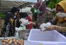 Wali Kota Surabaya Tri Rismaharini saat menyiapkan minuman di dapur umum yang didirikan oleh Pemkot Surabaya