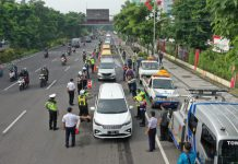 Proses sterilisasi kendaraan di perbatasan kota Surabaya