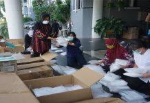 Salurkan Bantuan - Wali Kota Surabaya Tri Rismaharini saat melakukan pengemasan APD yang akan disalurkan kepada para Tenaga Kesehatan (Nakes) Di Kota Surabaya